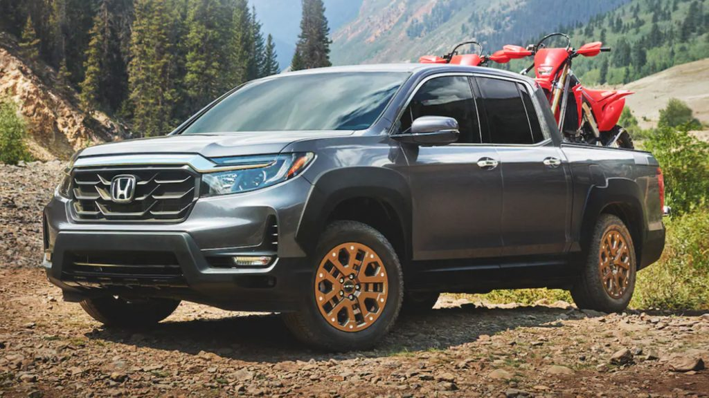 all-new 2022 Honda Ridgeline posing off-road with two honda dirt bikes in the pickup bed
