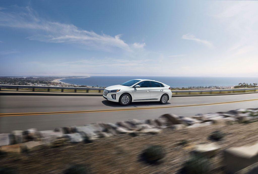 A white 2021 Hyundai Ioniq Electric driving, the 2021 Hyundai Ioniq Electric is an affordable electric car