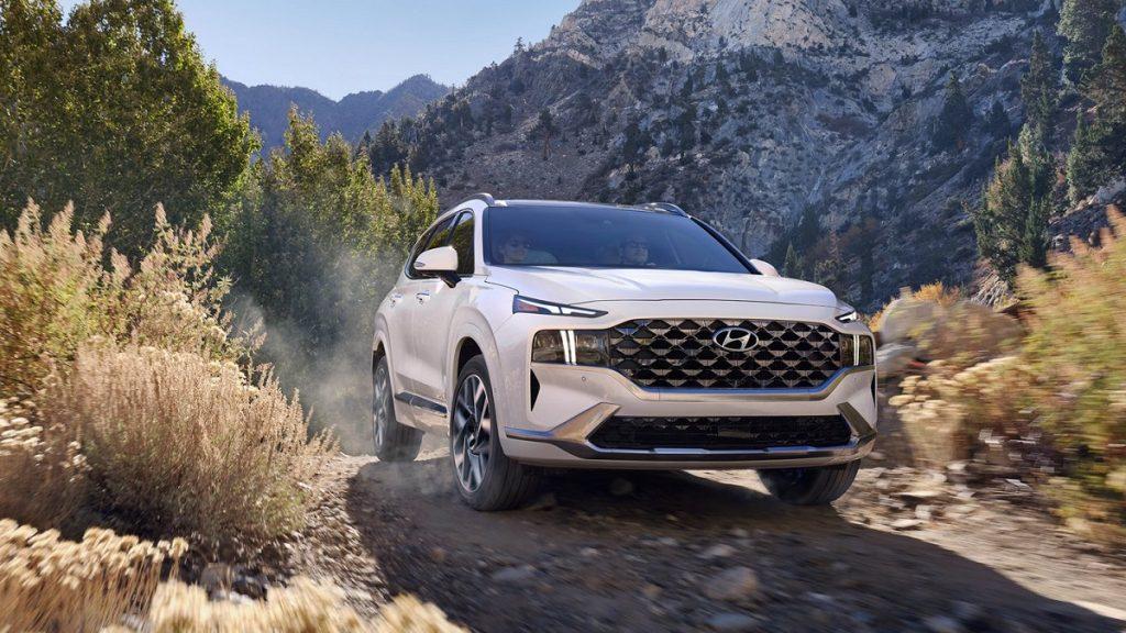 A white 2021 Hyundai Santa Fe drives through the mountains.
