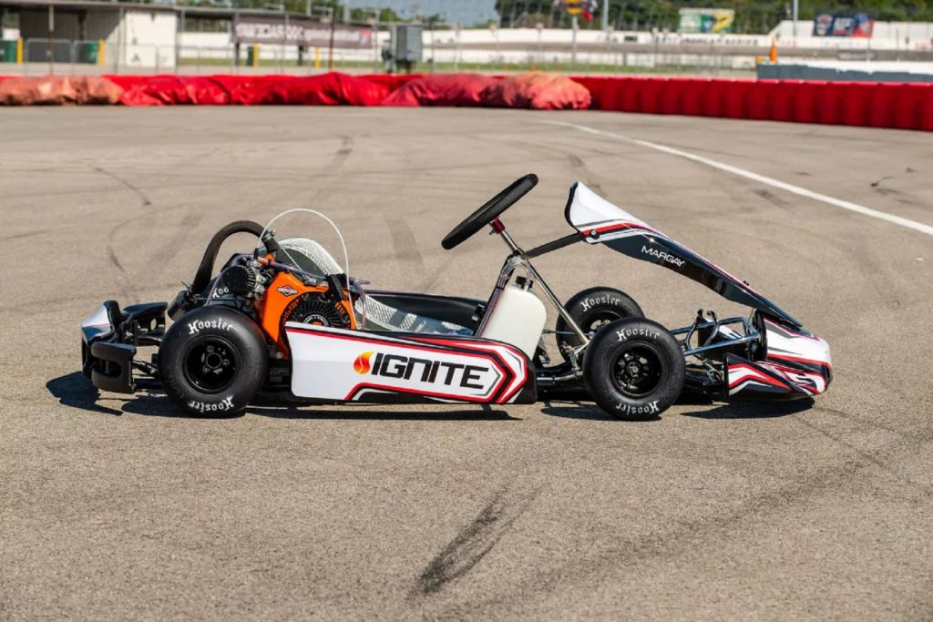 The side view of a white-red-and-black 2021 Ignite K3 racing kart on a racetrack