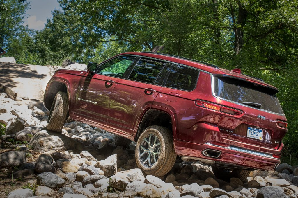 The rear 3/4 view of a red 2021 Jeep Grand Cherokee L Overland with Off-Road Group Package crawling up a rocky forest hill