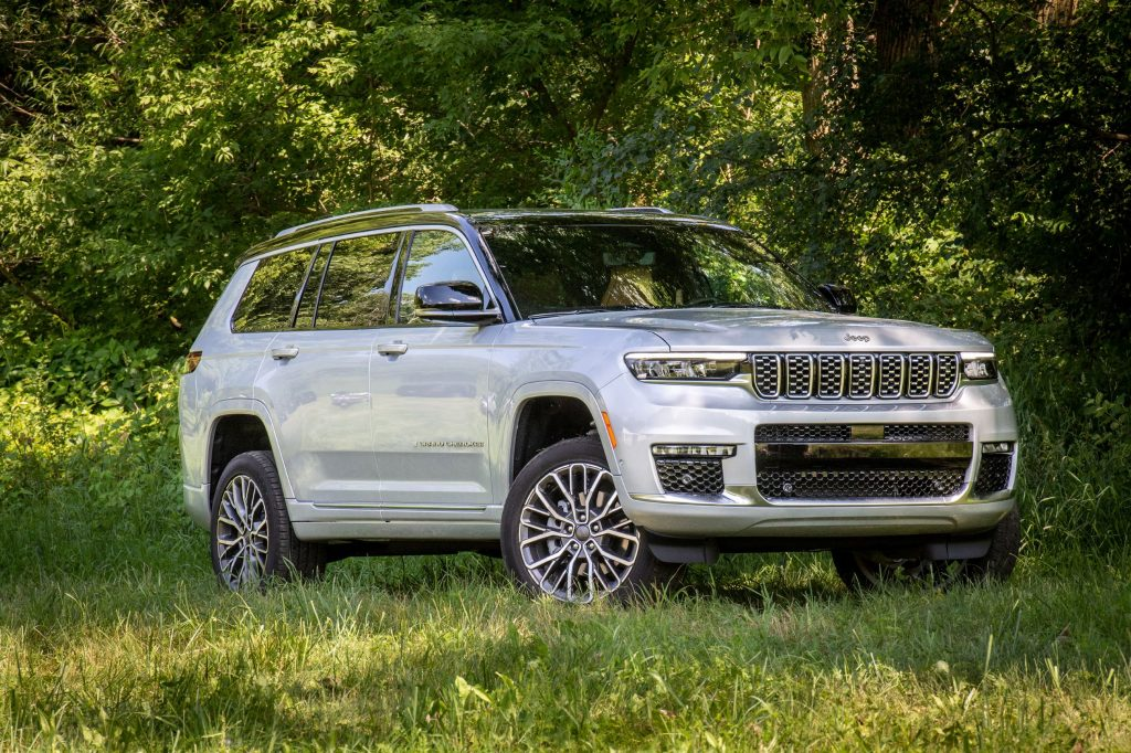 A white 2021 Jeep Grand Cherokee L Summit Reserve parked in the forest shade