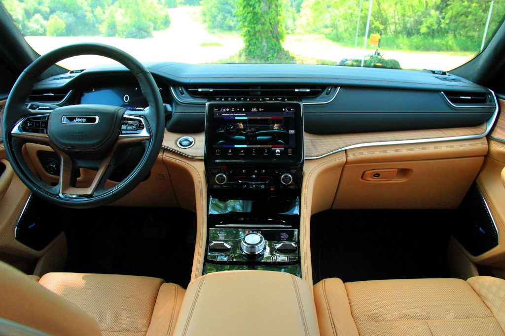 The tan-leather and wood-trimmed front interior of the 2021 Jeep Grand Cherokee L Summit Reserve