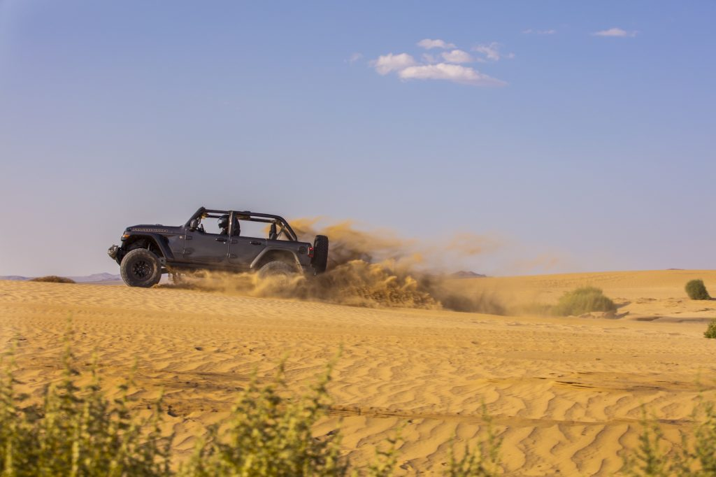 The 2021 Jeep Wrangler easily navigates a sand dune and is great for beach adventures