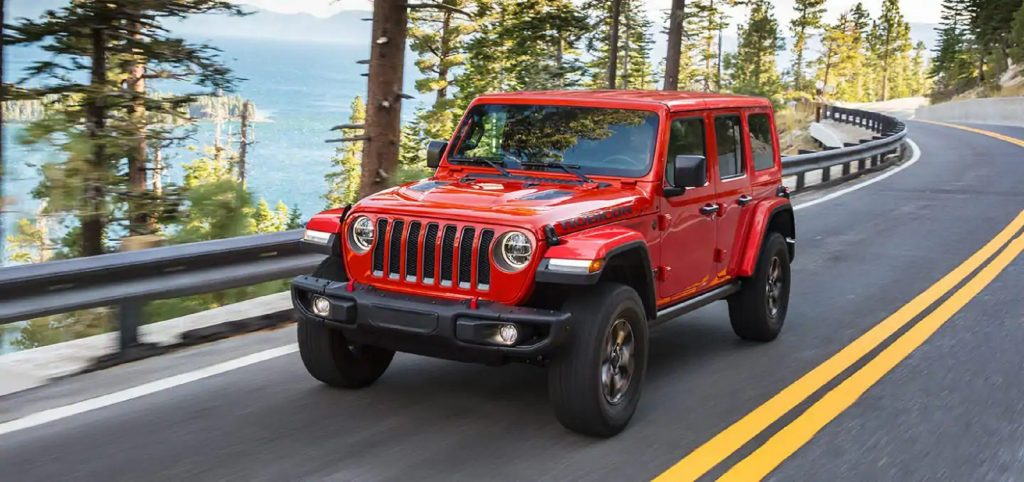 A red 2021 Jeep Wrangler Rubicon Unlimited drives on a forest road overlooking a lake