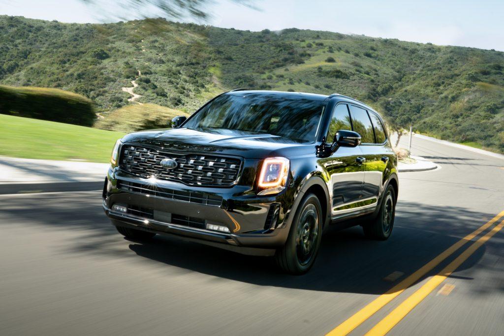 A black 2021 Kia Telluride Nightfall Edition midsize SUV travels on a two-lane through green hills