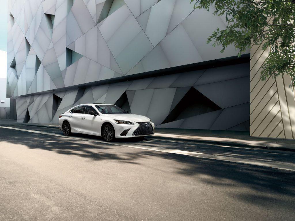 A white 2021 Lexus ES driving down an empty street
