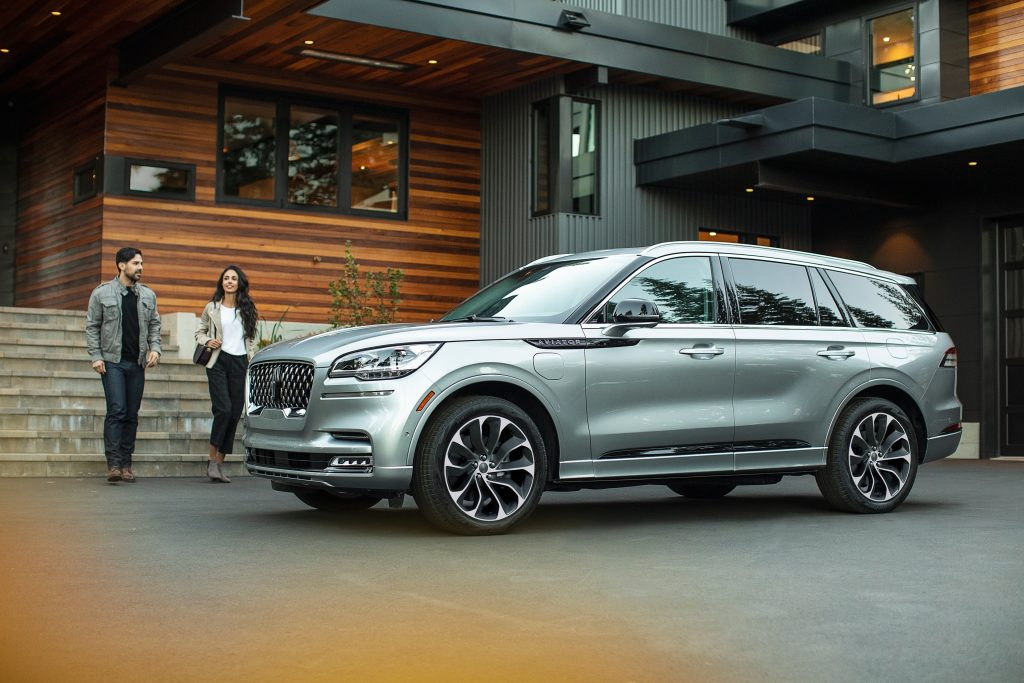 Two people walk up to a silver 2021 Lincoln Aviator Grand Touring plug-in hybrid parked by a wood-and-stone building