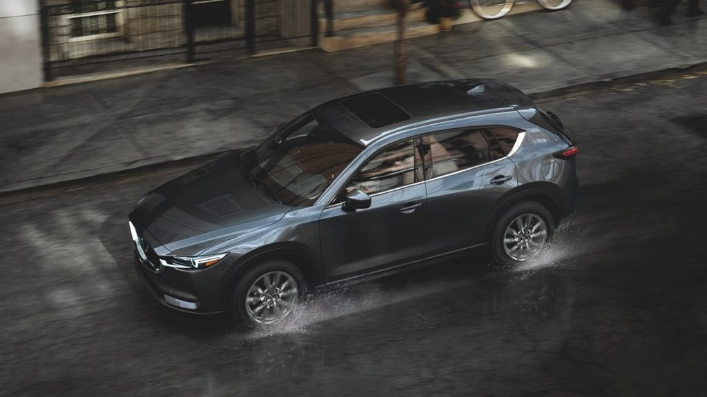 A dark colored Mazda CX-5 splashes through a puddle in the city.