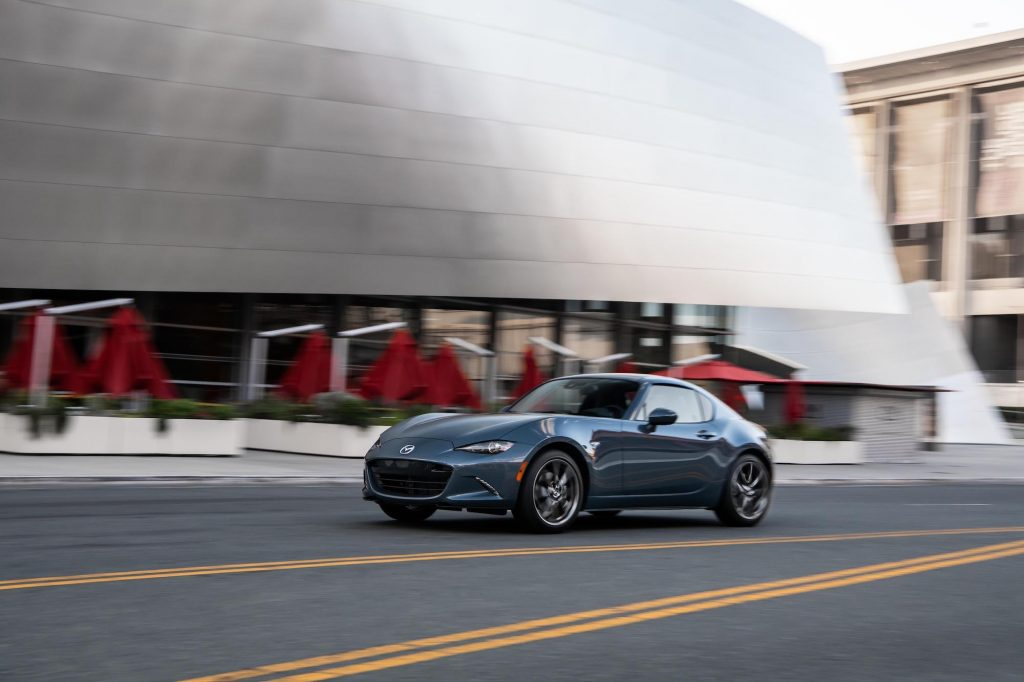 A 2021 Mazda MX-5 Miata RF sports car, with Polymetal Gray exterior paint, travels past a silver city building
