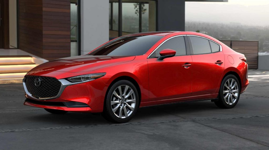 A red 2021 Mazda3 Premium by a white-and-brown-wood house