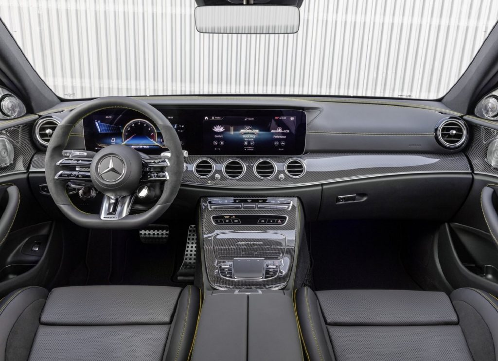 The black-leather-upholstered front seats and carbon-fiber-trimmed dashboard of a 2021 Mercedes-AMG E63 S