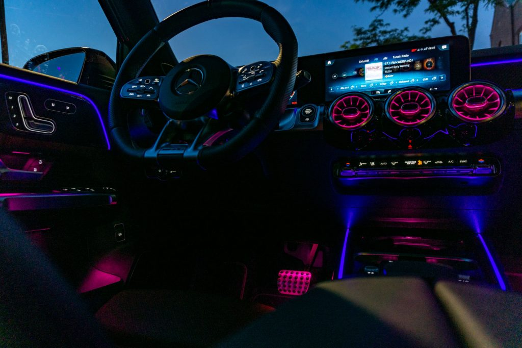 The driver's side front interior of a 2021 Mercedes-AMG GLB 35 with its ambient lighting turned on at night