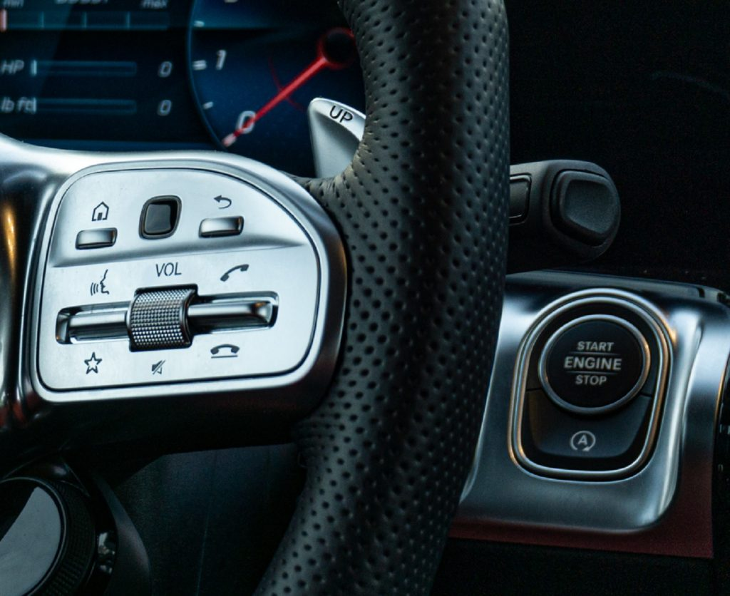 A close-up of the steering wheel, start button, and start-stop system defeat button in a 2021 Mercedes-AMG GLB 35