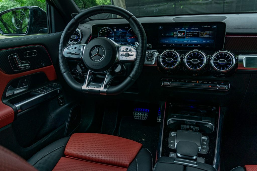 The red-and-black-leather interior of a 2021 Mercedes-AMG GLB 35 with its MBUX infotainment system active