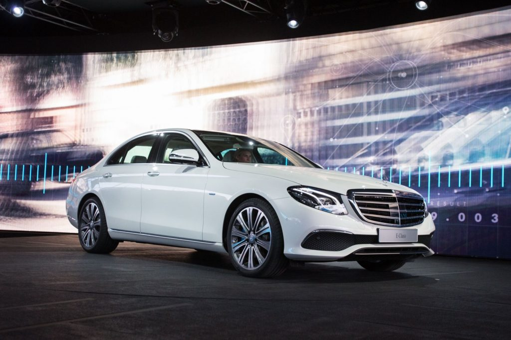 A white 2021 Mercedes-Benz E-Class sedan parked on a stage at an auto show