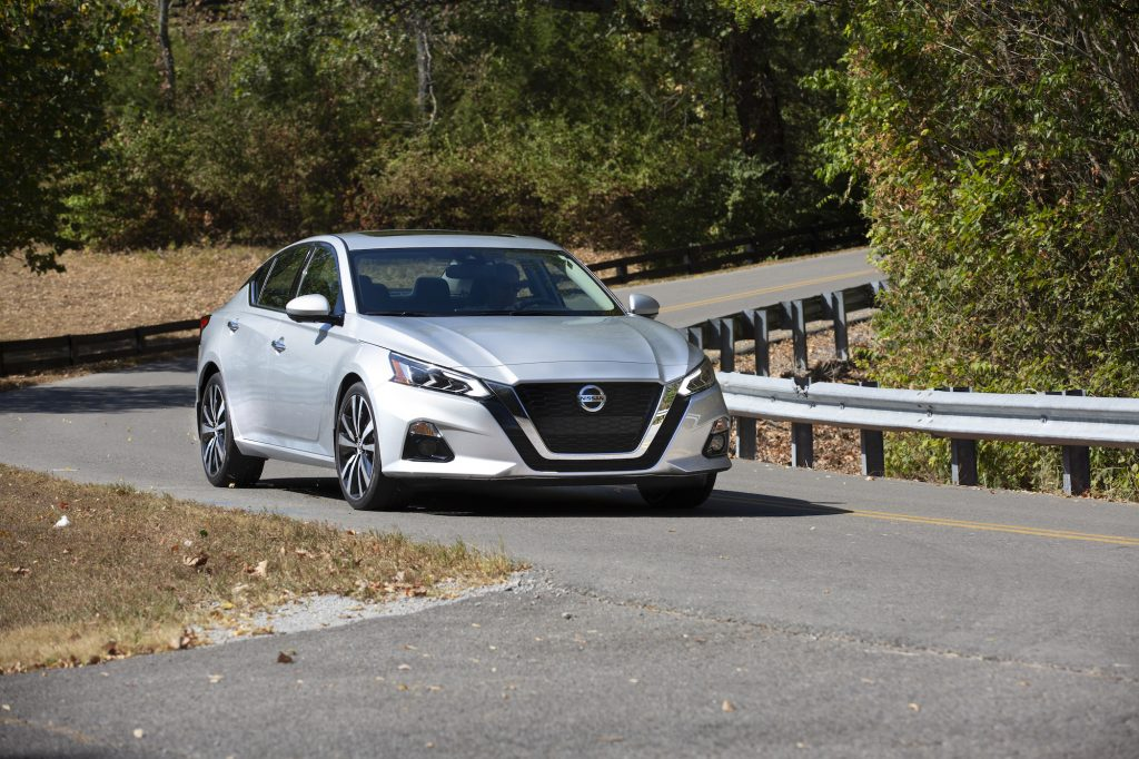 A silver 2021 Nissan Altima midsize sedan traveling on a curvy two-lane highway through trees
