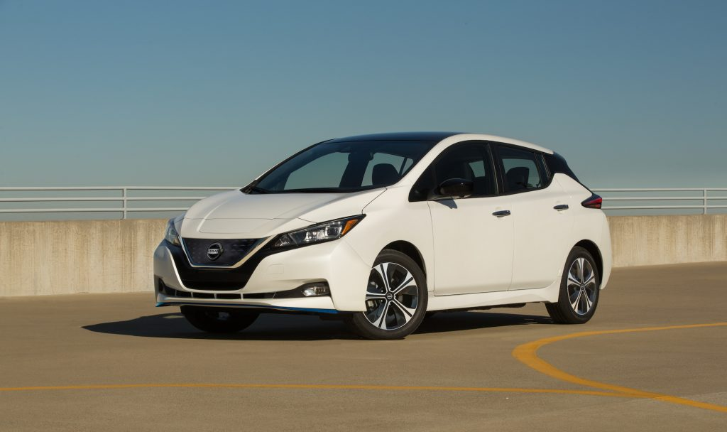 A white 2021 Nissan LEAF SV Plus electric car parked in a lot under a clear blue sky comes with a big discount for the 4th of july weekend