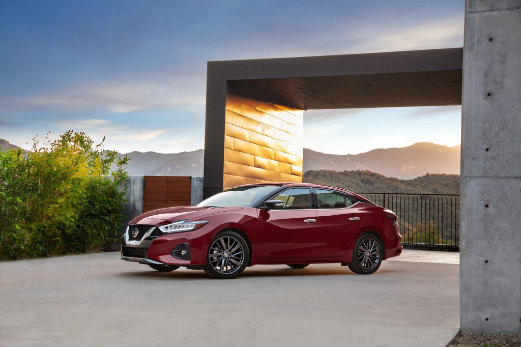 A red 2021 Nissan Maxima sedan parked outside a modern concrete home overlooking mountains