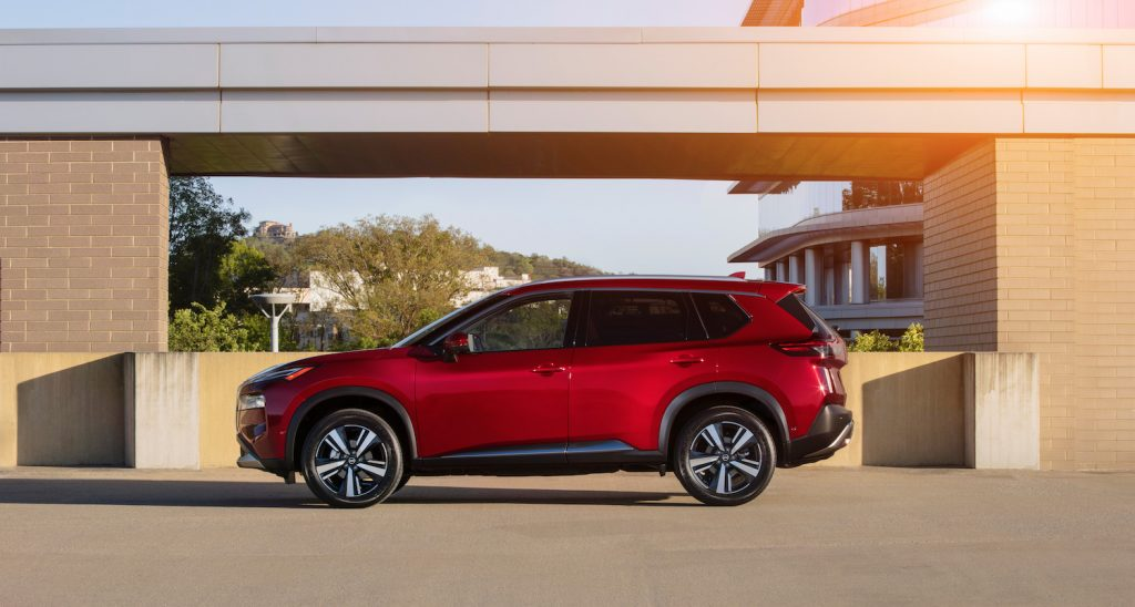 A red 2021 Nissan Rogue parked with the sun shining on it