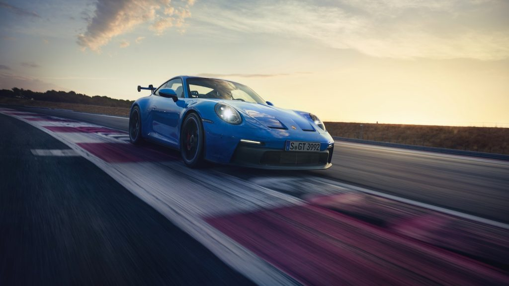 A blue 2021 Porsche 911 driving around a track, the 911 is the best new sports car for road trips