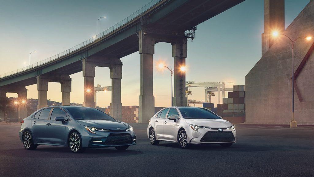 A gray 2021 Toyota Corolla XSE next to a white 2021 Toyota Corolla Hybrid LE parked underneath a city bridge