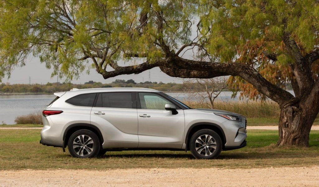 A silver 2021 Toyota Highlander XLE midsize SUV parked under a tree overlooking a body of water