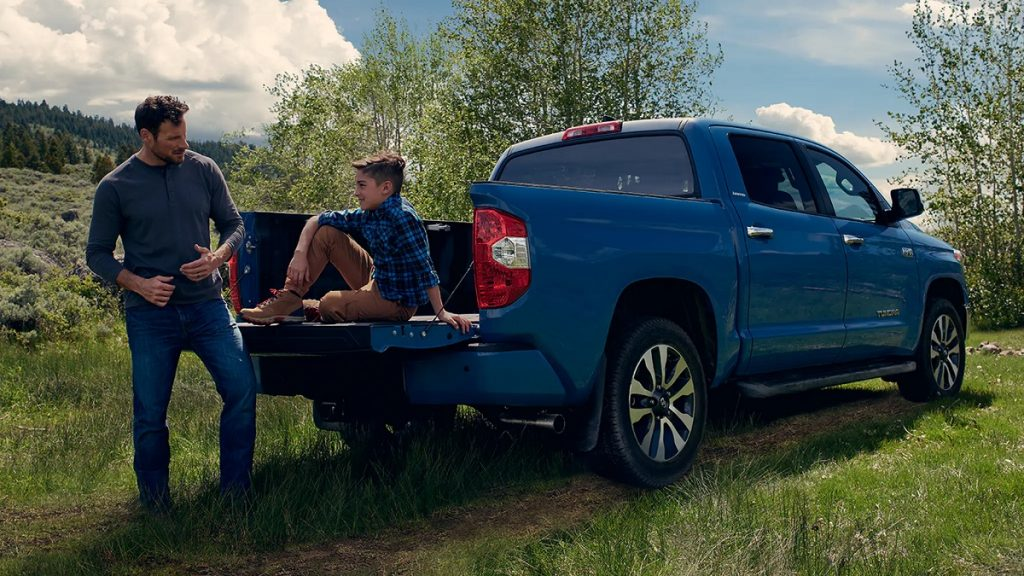 A father talks to his son who is sitting in the bed of a blue 2021 Toyota Tundra.