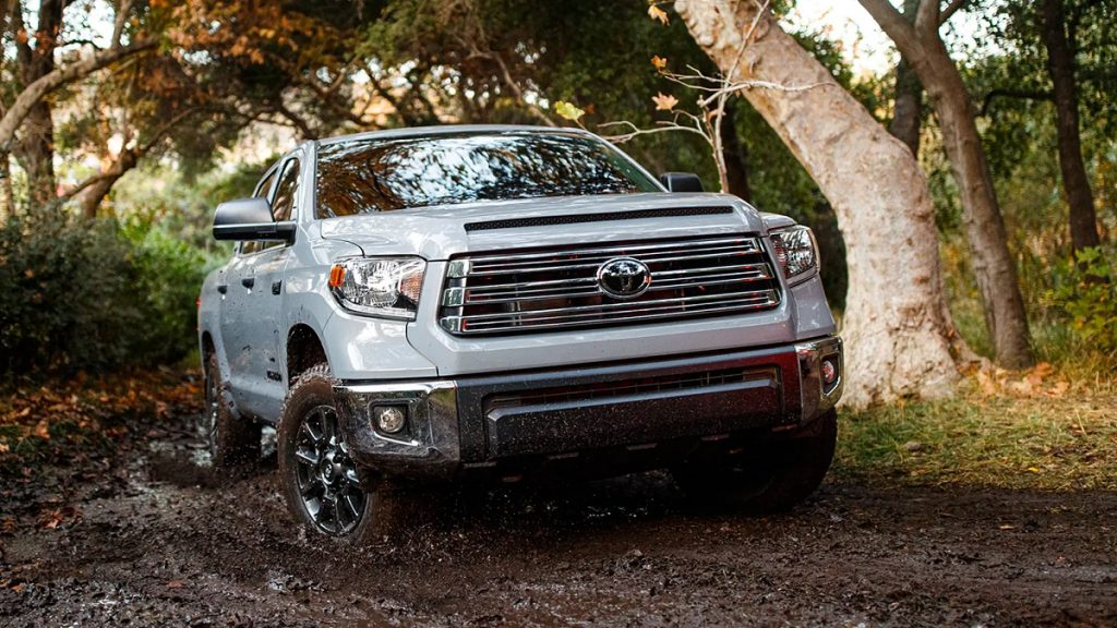 A white 2021 Toyota Tundra splashing through the mud in the woods.