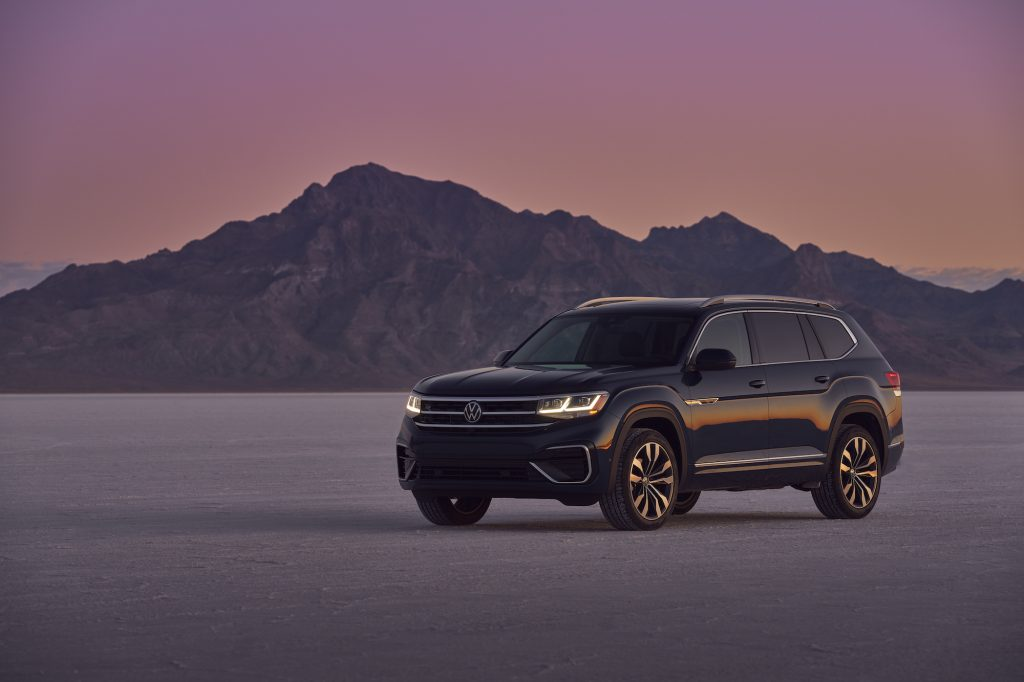 A black 2021 Volkswagen Atlas midsize SUV parked in front of mountains underneath a purple and orange sky