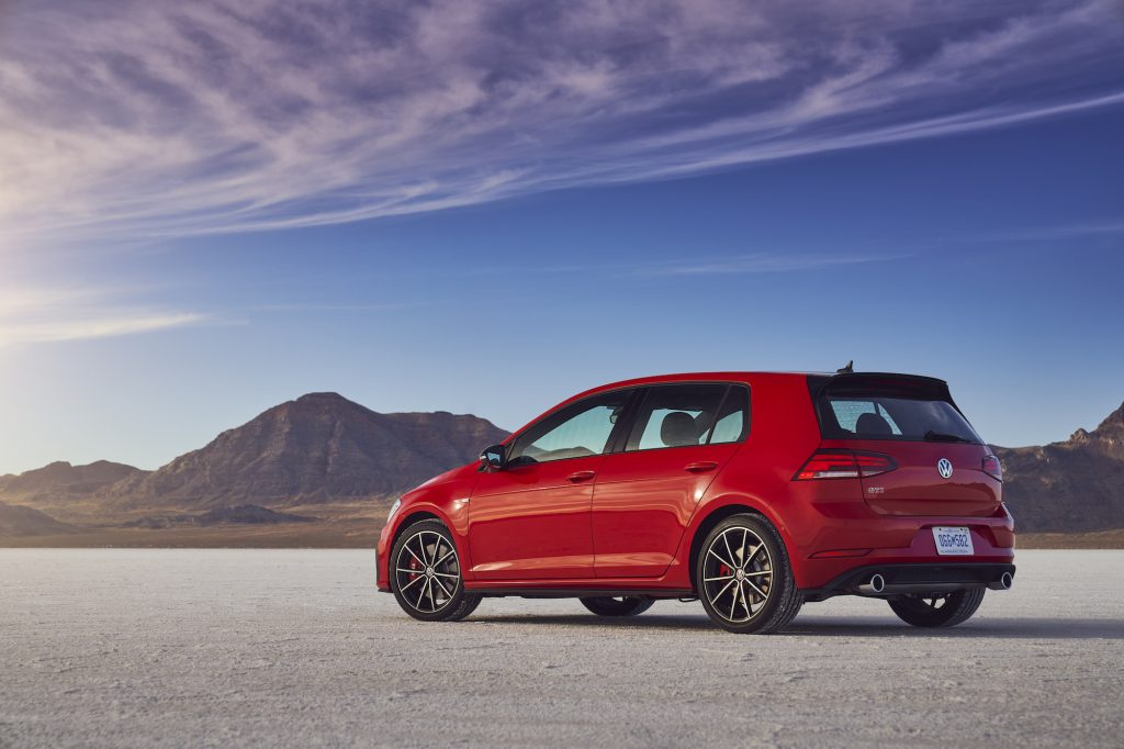 A red 2021 Volkswagen Golf GTI hatchback parked in a desert with mountains and blue sky