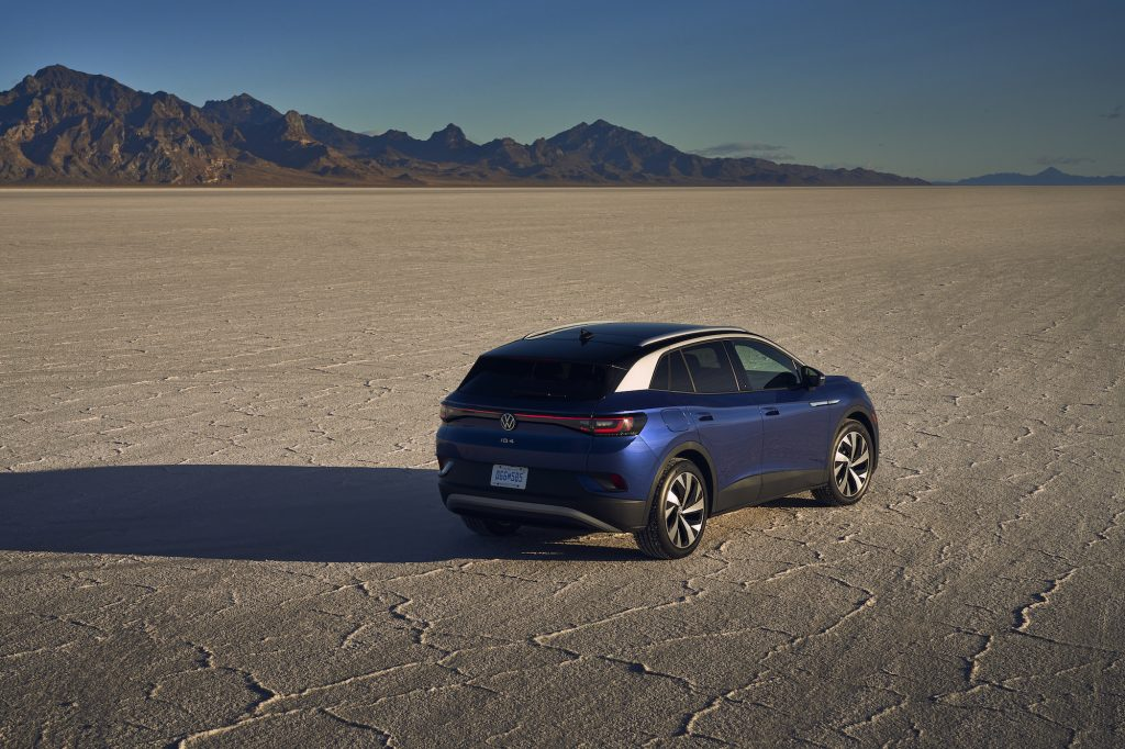 A blue metallic 2021 Volkswagen ID.4 Pro S electric SUV parked in a desert with mountains in the distance