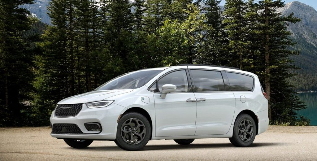 a white 2021 Chrysler Pacifica Hybrid parked outside in front of a scenic forested area