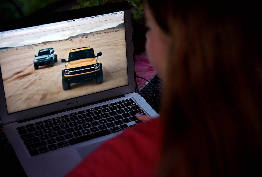 A person watching the 2021 Ford Bronco World Premier on a laptop.
