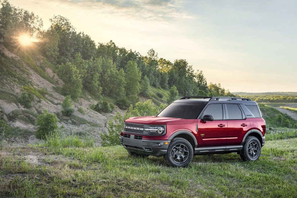 A red 2021 Ford Bronco Sport SUV parked outdoors in a wooded area
