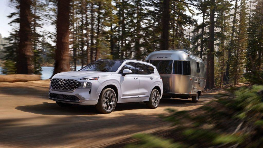 A white 2021 Hyundai Santa Fe towing an Airstream trailer in the woods