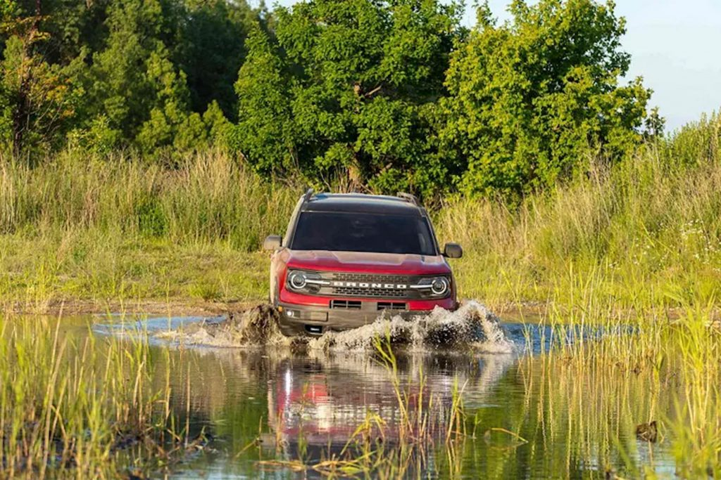 a red 2021 Ford Bronco driving through shallow water