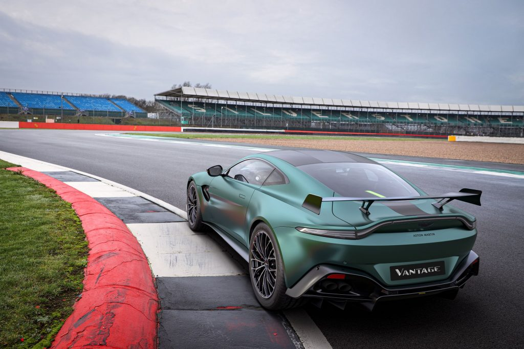 The rear 3/4 view of a green-and-black 2022 Aston Martin Vantage F1 Edition on a racetrack corner