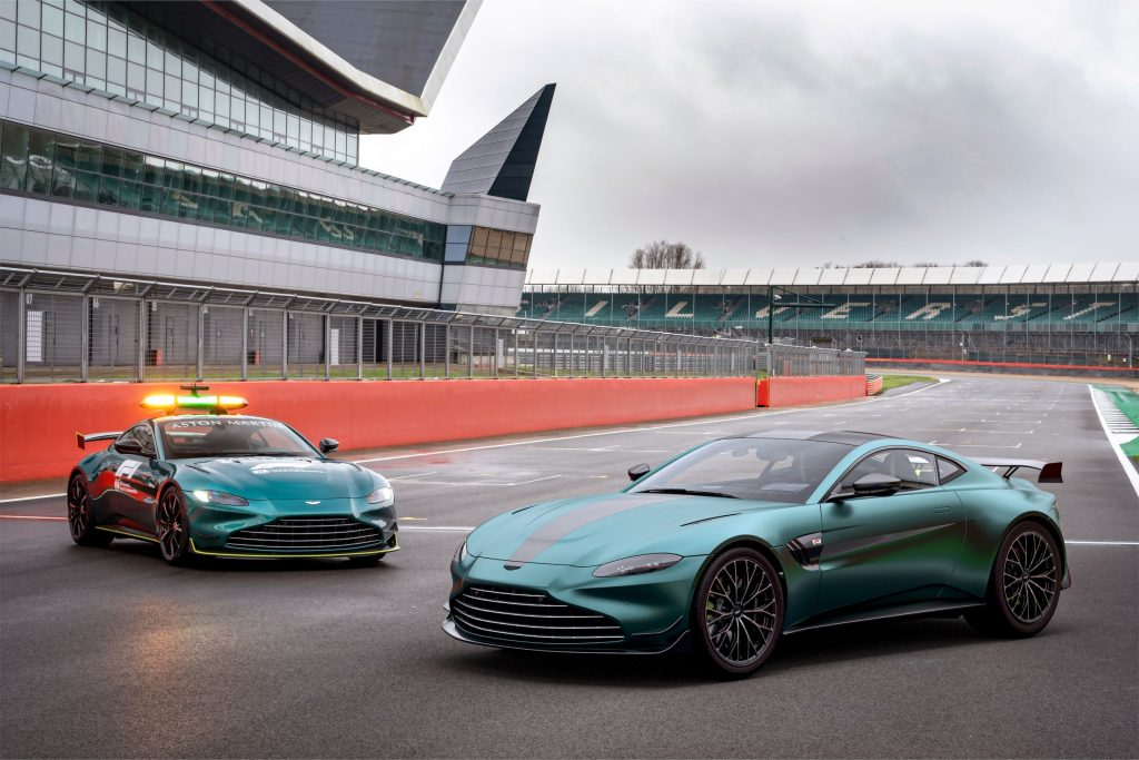 A green 2022 Aston Martin Vantage F1 Edition to the right of the green Vantage F1 safety car on a racetrack