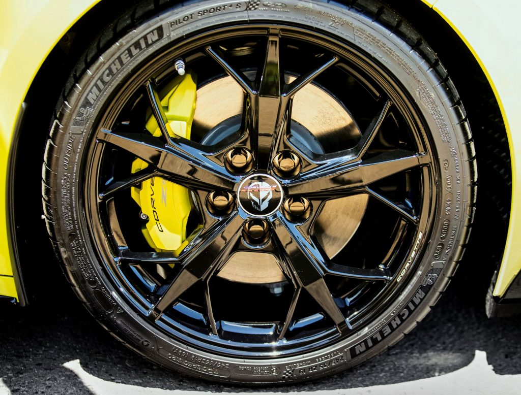 A close-up view of the yellow brake calipers and black wheels of a yellow 2022 Chevrolet Corvette IMSA GTLM Championship Edition