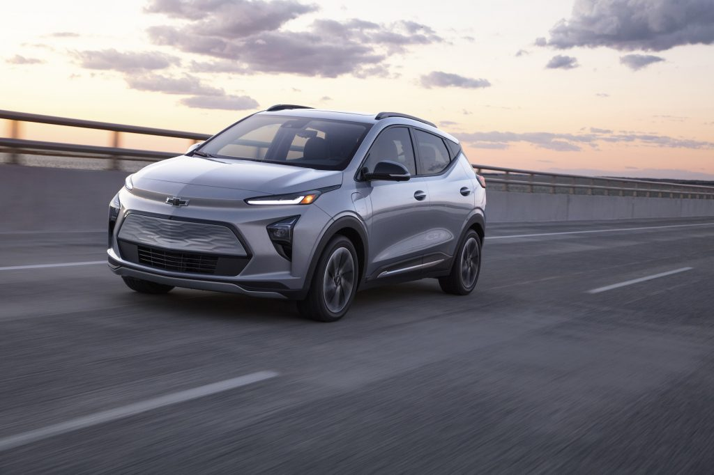 A silver 2022 Chevrolet Bolt EUV electric crossover traveling on a highway as the sun sits low in a mostly clear sky