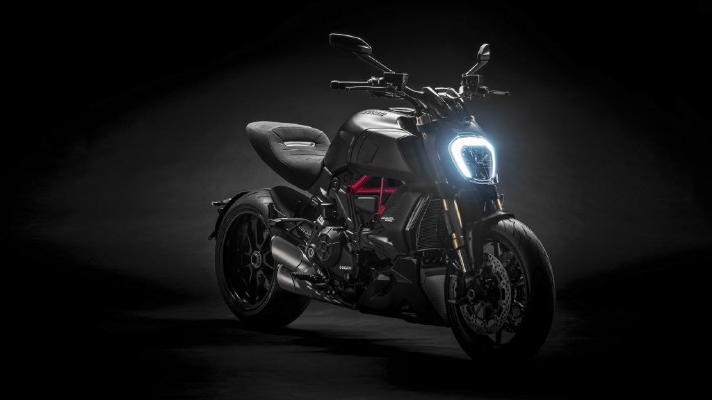 A black-and-red 2022 Ducati Diavel 1260 S with its LED headlight on