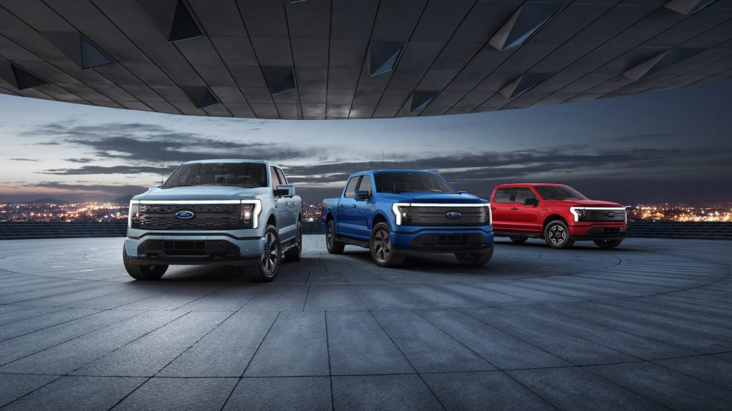2022 Ford F-150 Lightning Platinum, Lariat, and XLT pre-production models overlooking a city skyline at night