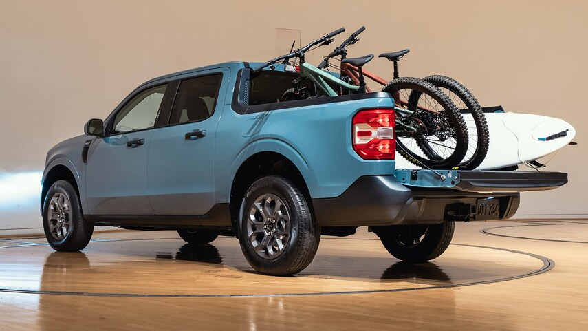 a blue 2022 ford maverick with bikes and a surf board in the bed