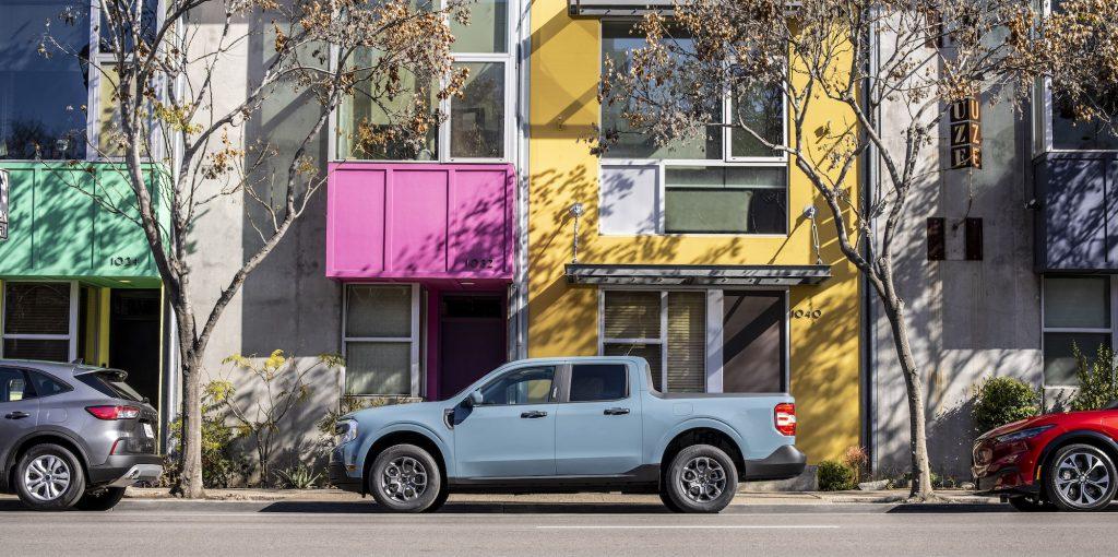 A powder-blue 2022 Ford Maverick Hybrid XLT pickup truck paked on a city street outside a colorful building