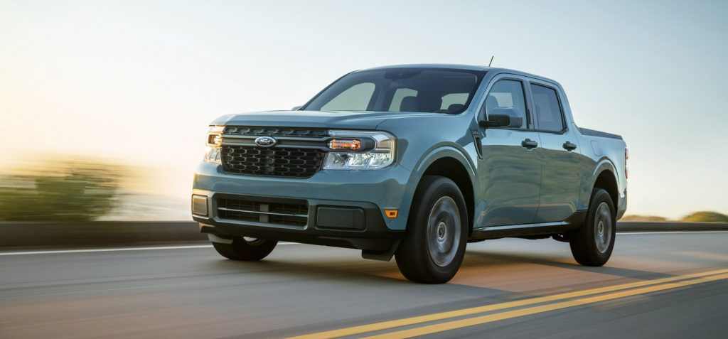A powder-blue 2022 Ford Maverick Hybrid XLT compact pickup truck travels on a two-lane highway