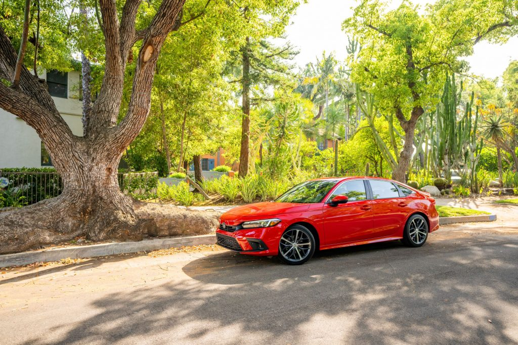 The side 3/4 view of a red 2022 Honda Civic Sedan Touring parked on a tree-lined street by a house