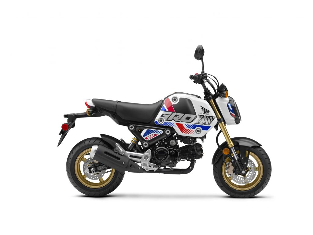 The side view of a 2022 Honda Grom in white-red-and-blue RHP livery with gold elements