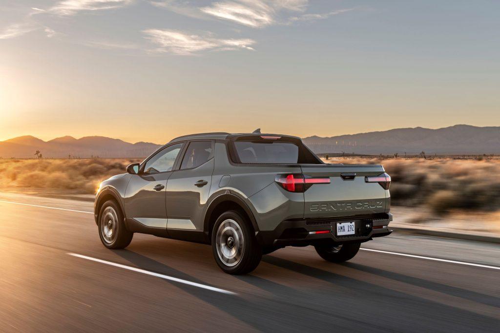 The rear 3/4 view of a gray-green 2022 Hyundai Santa Cruz driving down a desert road