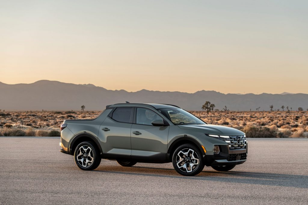 A gray-green 2022 Hyundai Santa Cruz parked on a paved road in the desert